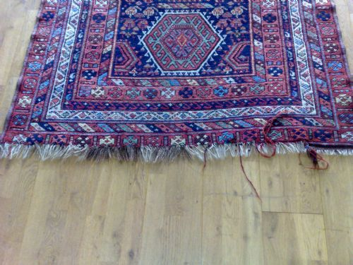 Frayed fringes to an antique Kurdish rug
