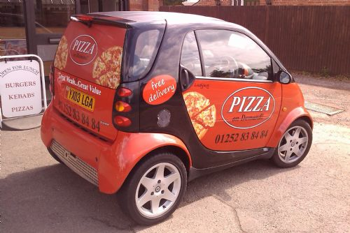 Graphics on Pizza Smart car including contravision window graphics