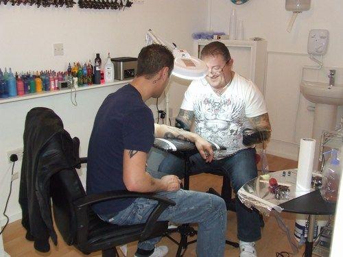 Kat Stevens tattooing a client