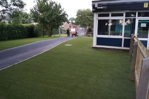 School in West Sussex once completed, with new roadway and grass areas either side.